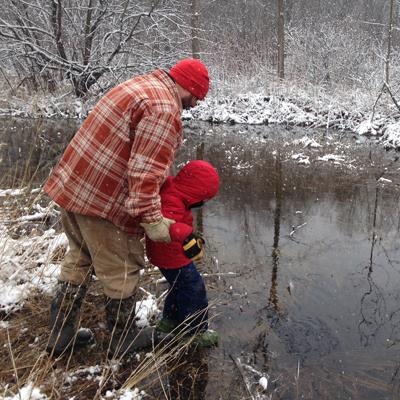 Man showing child a pond