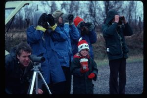 Group looking with binoculars outside
